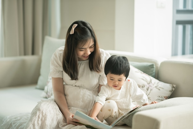 Mãe e filha lendo um livro na sala