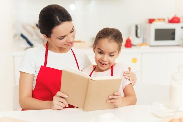 Mãe e filha lerem o livro. bolo para a família.