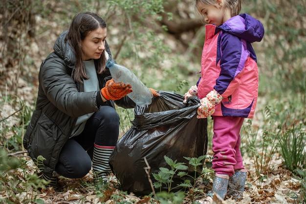 Mãe e filha limpam a floresta de plástico e outros detritos.