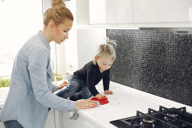 Mãe e filha limpam na cozinha