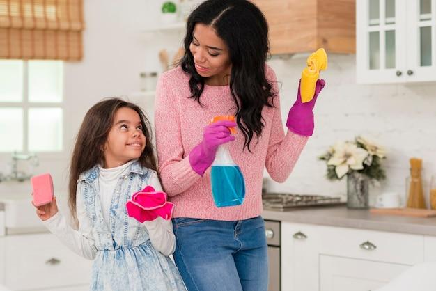 Mãe e filha limpando a casa