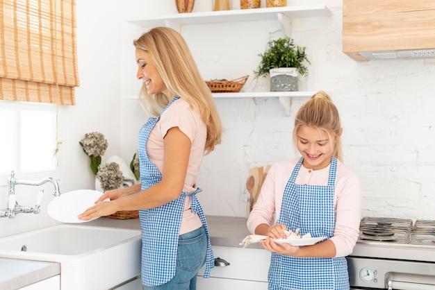 Mãe e filha limpando pratos