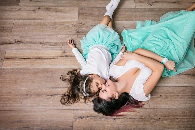 Mãe e filha lindas e felizes com saias turquesa deitadas no piso laminado, vista superior da casa