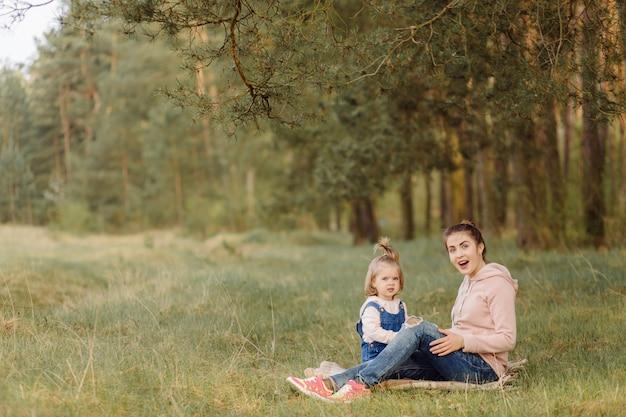 Mãe e filha lindas e felizes, divertindo-se na floresta