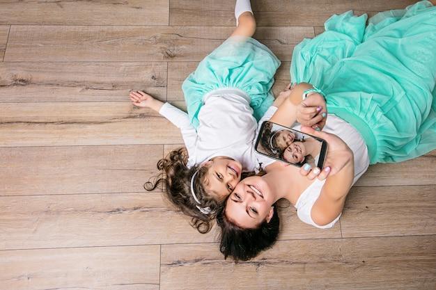 Mãe e filha lindas e felizes fazendo selfie em saias turquesa, deitadas no piso laminado