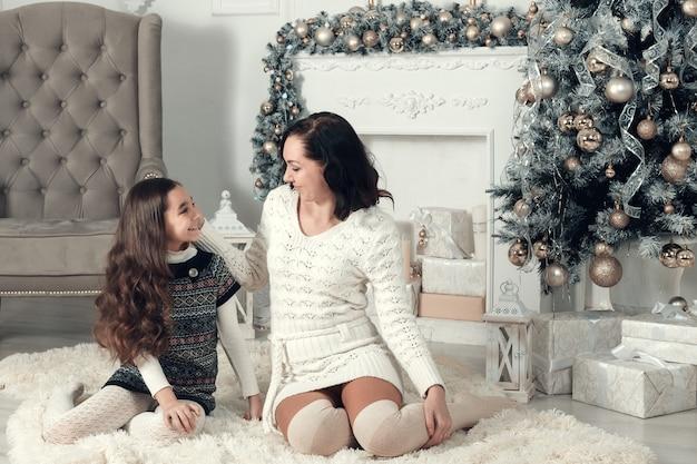 Mãe e filha, localização em um sofá na sala de natal decorada