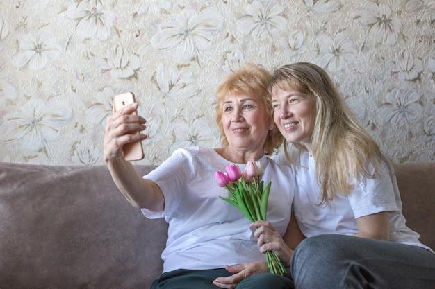 Mãe e filha loira adulta em camisetas brancas estão sorrindo e fazendo selfie com buquê de tulipas cor de rosa em casa. conceito de dia das mães