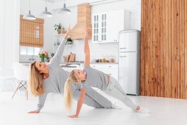 Mãe e filha malhando indoor