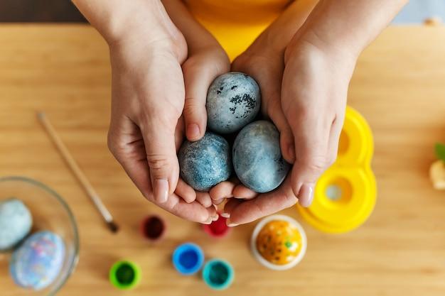 Mãe e filha mãos segurando ovos de páscoa de pintura. feminino e criança mão com ovo sobre a mesa com tintas e pincéis. família feliz se preparando para a páscoa. close up, foco seletivo