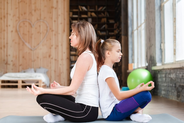 Mãe e filha meditando de costas