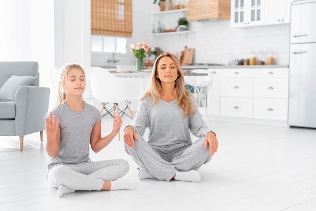 Mãe e filha meditando interior