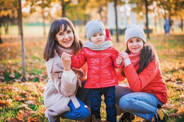 Mãe e filha menina brincando juntos no outono andar na natureza ao ar livre. jogos ativos de família feliz, estilo de vida no parque outono amarelo. movimento, desfocagem, foco seletivo.
