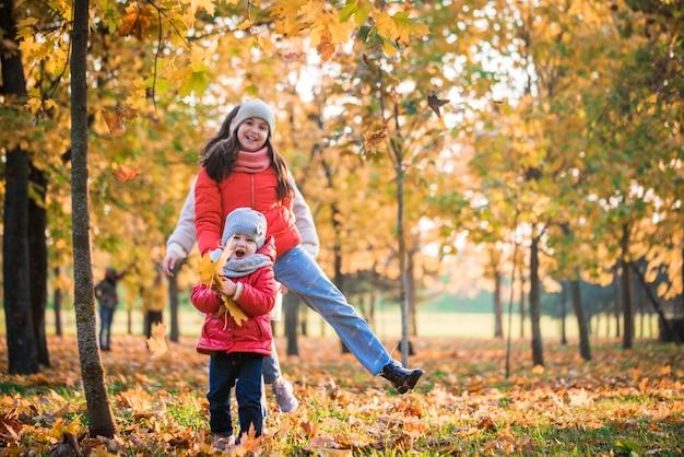Mãe e filha menina brincando juntos no outono caminhada ao ar livre.