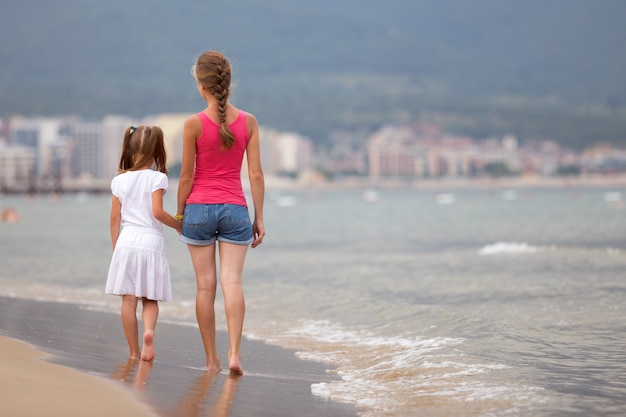 Mãe e filha menina caminhando juntos na praia de areia na água do mar no verão com os pés descalços nas ondas quentes do oceano.
