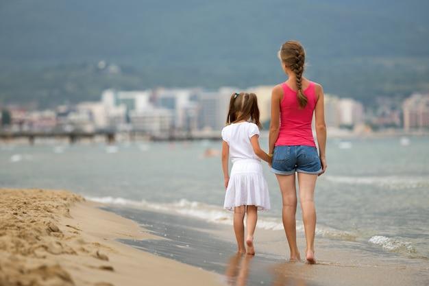 Mãe e filha menina caminhando juntos na praia de areia na água do mar