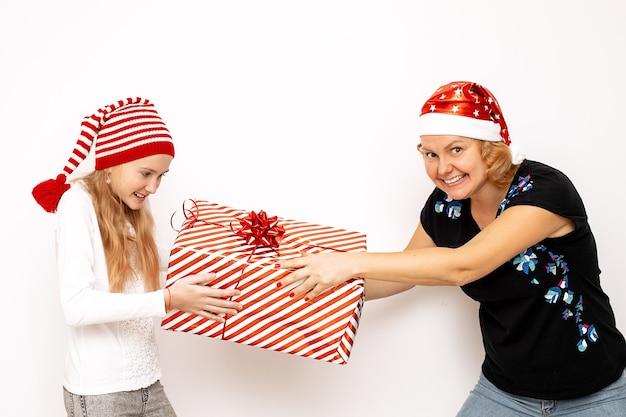 Mãe e filha menina com chapéus de papai noel estão se divertindo, lutando por uma grande caixa vermelha de presente. conceito de férias, diversão para o natal