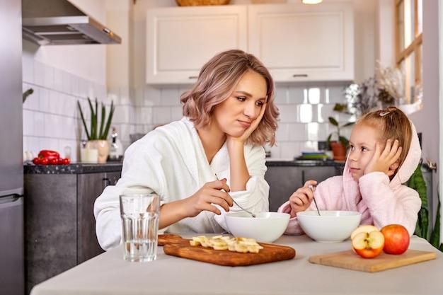 Mãe e filha menina sentadas não querem comer de manhã