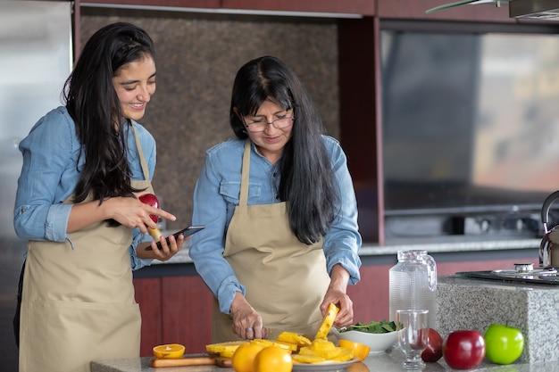 Mãe e filha mexicana cozinhando na cozinha procurando a receita no smartphone