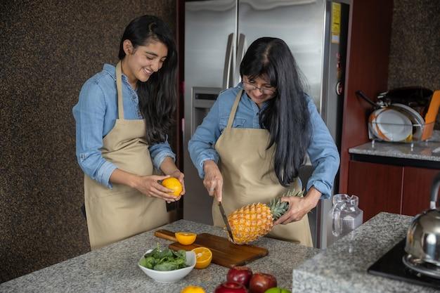 Mãe e filha mexicanas cortando frutas na cozinha e rindo, família e dia das mães