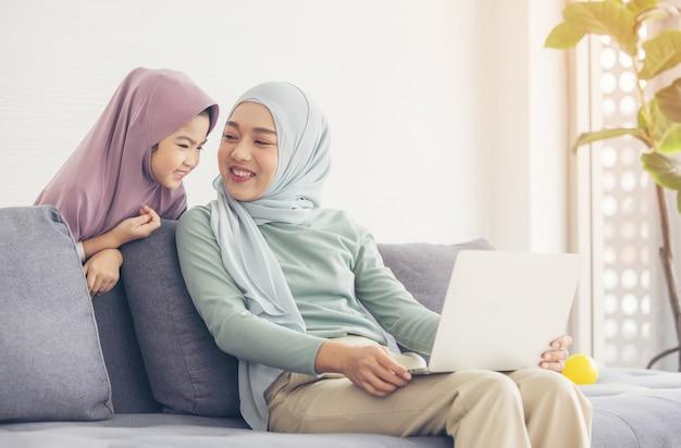 Mãe e filha muçulmanas asiáticas sorrindo ao usar um laptop juntas, navegando na internet ou assistindo a um filme