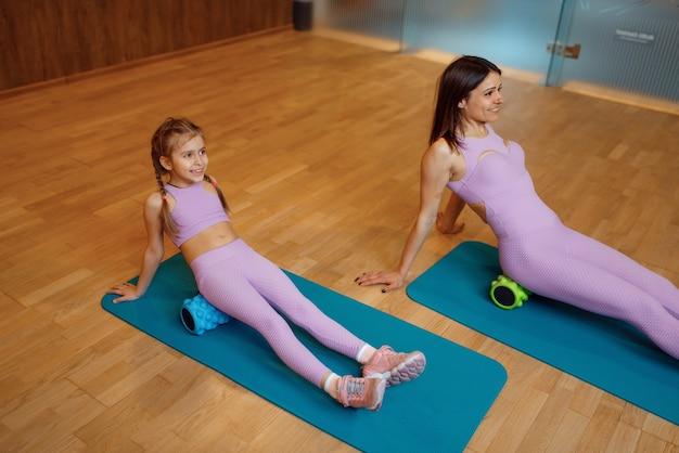 Mãe e filha na academia, exercício com rolos