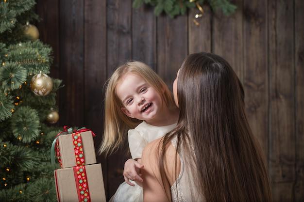 Mãe e filha na árvore de natal em um fundo de madeira
