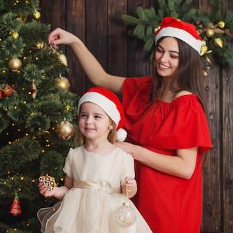 Mãe e filha na árvore de natal em uma madeira escura