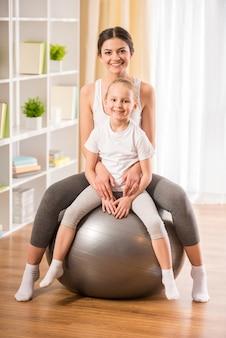Mãe e filha na bola de fitness em casa.