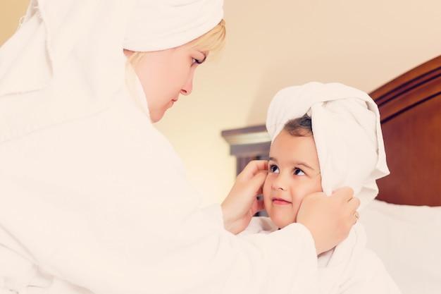 Mãe e filha na cabeça toalhas depois do banho na cama em casa