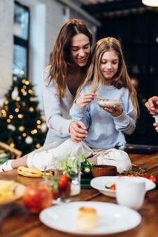 Mãe e filha na cozinha. menina sentada na mesa, fim de semana de inverno, clima de férias.