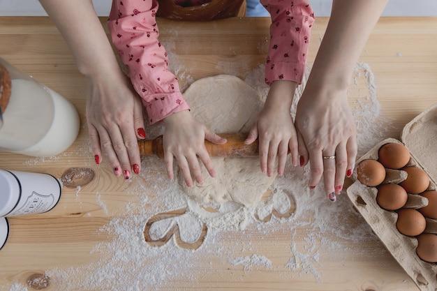 Mãe e filha na cozinha preparam comida com farinha e desenham corações na farinha