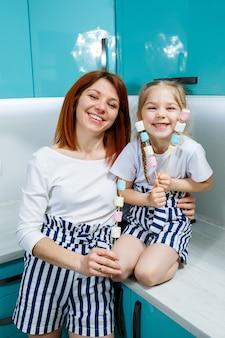 Mãe e filha na cozinha turquesa estão brincando com marshmallows. relacionamentos familiares encantadores. conceito de família feliz