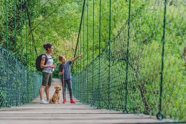 Mãe e filha na floresta andando sobre a ponte de madeira