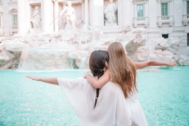 Mãe e filha na fonte de trevi, roma, menina fazendo um desejo de voltar,