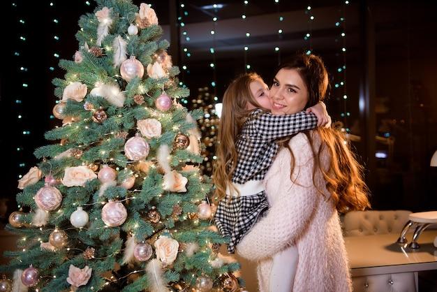 Mãe e filha na frente da árvore de ano novo em casa.
