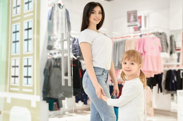 Mãe e filha na loja com roupas para crianças.