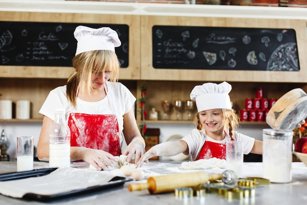 Mãe e filha nas mesmas roupas se divertem preparando uma massa em uma cozinha aconchegante