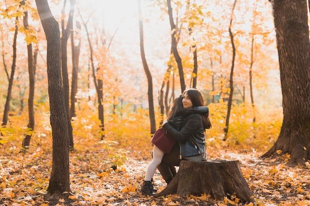 Mãe e filha no parque de outono no outono