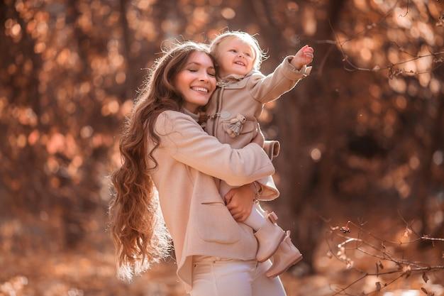 Mãe e filha no parque outono para passear