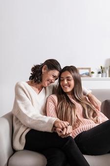 Mãe e filha no sofá, de mãos dadas