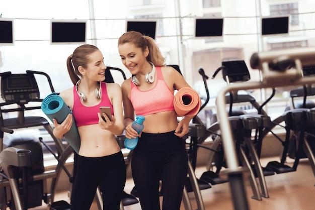 Mãe e filha no sportswear com tapetes em pé no ginásio.