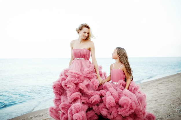 Mãe e filha no vestido rosa na praia