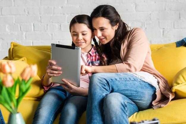 Mãe e filha olhando em um tablet digital