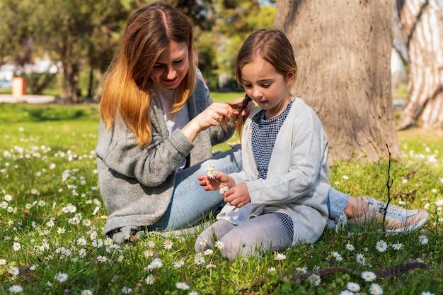 Mãe e filha olhando flores