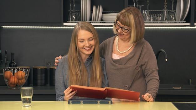 Mãe e filha olhando para álbum de família e sorrindo