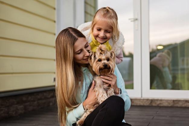 Mãe e filha olhando para cachorro