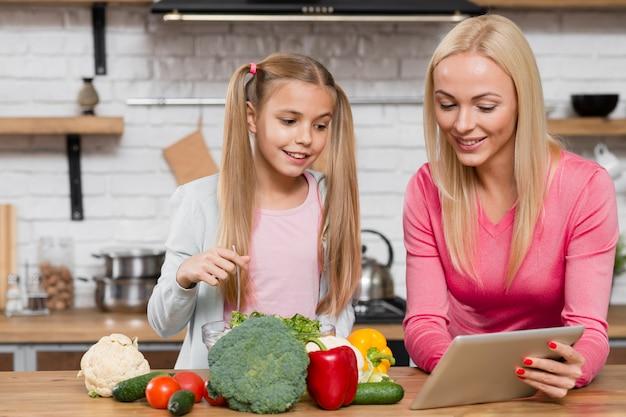 Mãe e filha olhando para um tablet digital