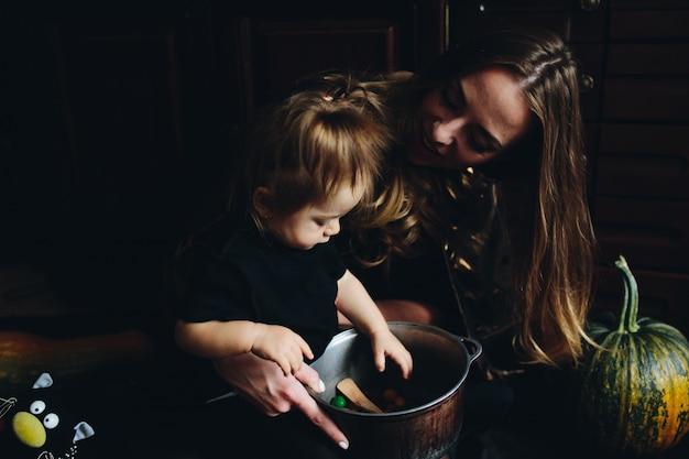 Mãe e filha olhando para uma tigela de doces