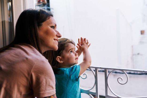 Mãe e filha olhando pela janela da casa