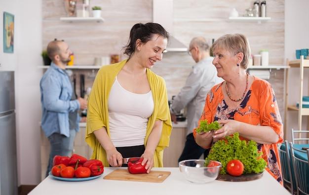 Mãe e filha olhando uma para a outra enquanto fazem salada de legumes frescos. marido cozinhando.